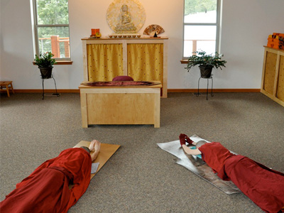 Venerable Samten and Venerable Jampa prostrating in front of the Abbey altar.