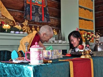 Abbey guest receiving a tsa-tsa from Venerable Chodron.