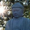Statue of a Buddha in front of a setting sun.