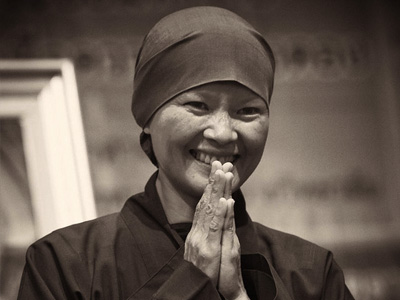 A nun smiling with palms together.