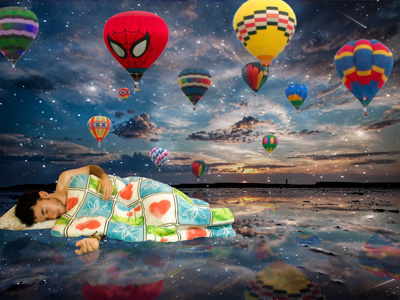 A man covering himself with blanket and sleeping in a seascape and different colors of air balloons in the sky.