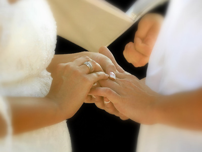 Couple exchanging rings at wedding ceremony.