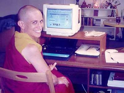 Venerable Chodron sitting at her computer desk, smiling.