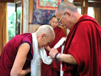 Venerable Chodron bowing to His Holiness the Dalai Lama.
