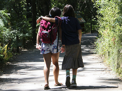 Two girls walking down a path, one with her arm around the other.