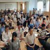 alot of people meditating in a hall.