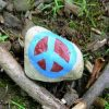A blue and red peace sign painted on a rock.