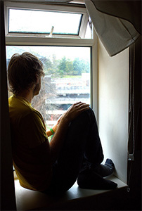 Young man sitting on window sill, staring out window.