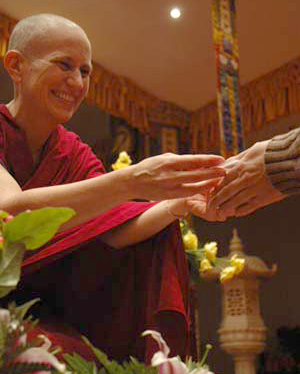 Venerable Chodron giving mani pills to a retreatant.