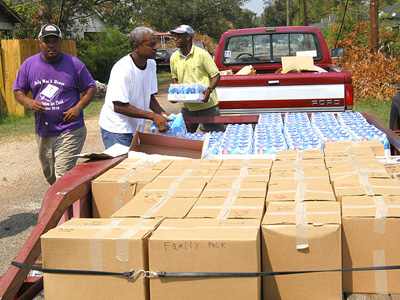 Volunteers distributing bottles of water from the back of a pickup truck.