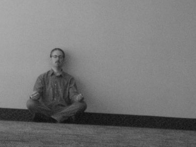 Black and white photo of man sitting on floor, meditating.