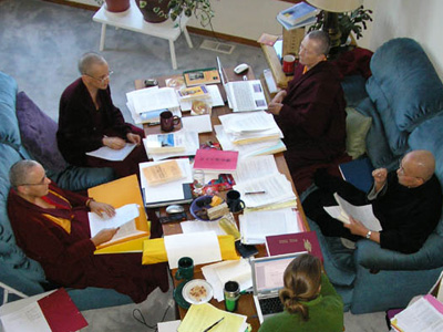 Ven. Chodron, Ven. Jampa Tsedroen , Ven. Heng-Ching Shih and Ven. Lekshe Tsomo sitting and discussing on a table full of papers.