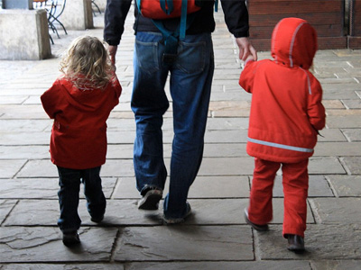 Father walking hand-in-hand with two children.
