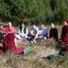 A group of monastics and laypeople outside having a group discussion.