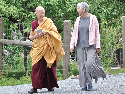 Venerable Chodron walking outside with Abbey guest, Tanya.