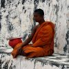 Thai monk sitting outside next to alms bowl, meditating.