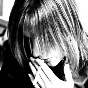 A black and white photo of a woman bending down her head smoking a cigarette, her hair covering her face.