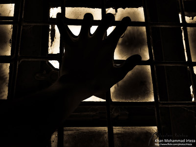 A hand gripping at the window grills in a dark place.