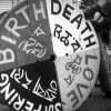 Black and white photo of a big wheel with the words-Birth, Death, Love and Suffering.