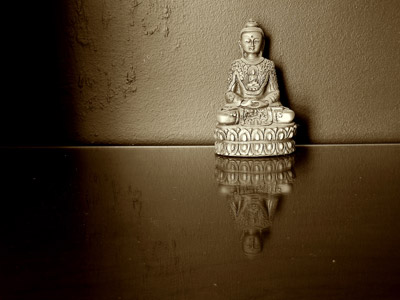 A buddha statue with reflecting image of the buddha on the surface.