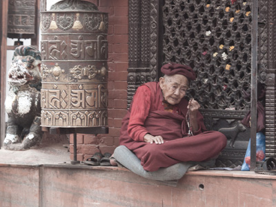 An old woman holding a mala reciting mantra.