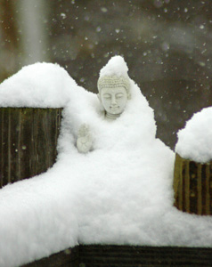 A statue of a buddha covered in snow.