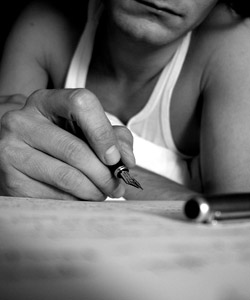 A man wearing a singlet using a fountain pen to write a letter.