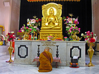 A bhikkhuni kneeling into front of a buddha statue praying.