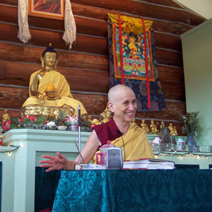 Venerable Chodron teaching the Dharma and smiling very happily.