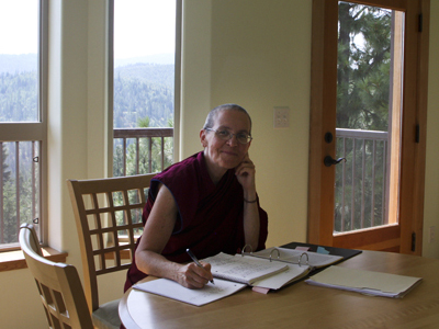 Venerable Thubten Semkye sitting at a table, writing.