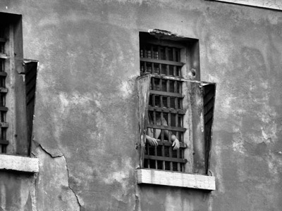 A man standing in a prison highly grill window.