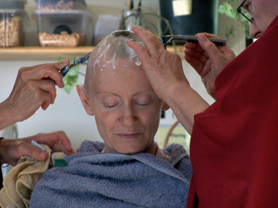 Venerable Samten with eyes closed while two nuns shave her head.