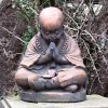 Copper monk sitting in a praying position.