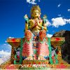 Colorful statue of Maitreya against blue sky in Ladakh.