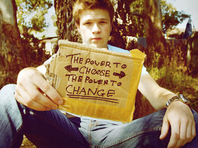 A guy sitting down on grass, his hand holding a cardboard with the words: The power to choose The power to change.