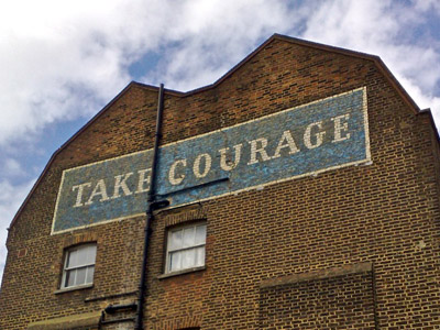 A building with the words Take Courage painted on the wall.