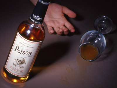 An alcohol bottle with the label Poison and a wine glass with some alcohol inside, a hand in the background.