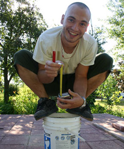 Carl squatting on a pail, taking a measuring tape and smiling.