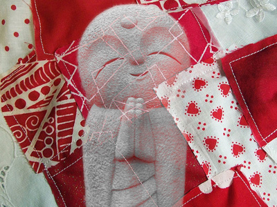 Jizo over a red and white patchwork quilt.