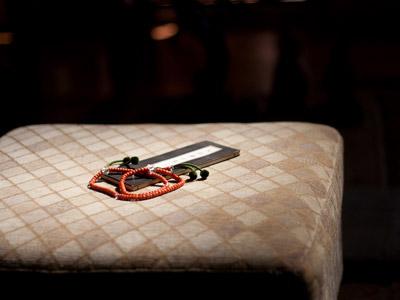 Mala and a sutra on a biege cushion.