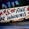 Hand-painted sign that says '$5.00 for whining'.