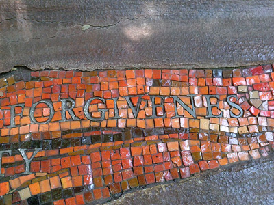 The word 'forgiveness' written into red and orange tile.