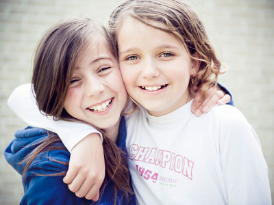 2 young girls putting their hand on each other shoulder and smiling happily.