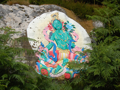 A painting of the green tara on a rock