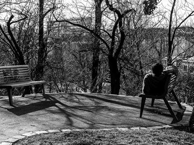 Homeless man lying on a park bench.