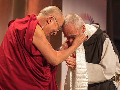 His Holiness touching his forehead to the head of a Catholic monk.
