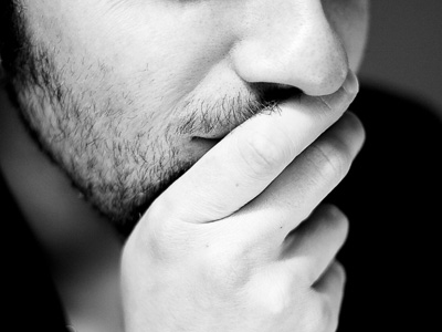 A man using his hand shielding his mouth, in deep thinking.