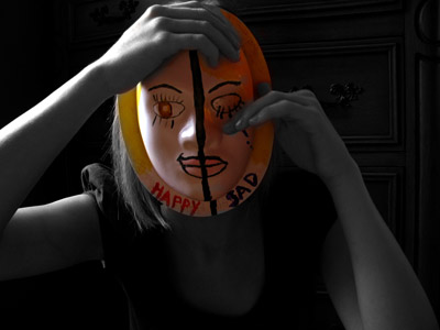 A woman wearing a mask covering her face, one side of the mask with an open eye and the word Happy and the other side of the mask a crying eye with the word Sad.