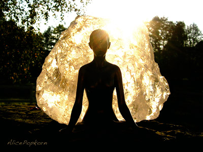 A big bubble wrapping a  woman who is meditating.