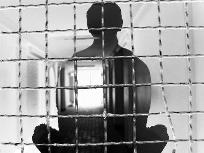 Transparent silhouette of man meditating behind prison bars.